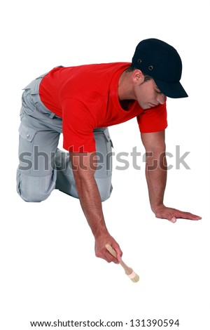 A male painter on all fours. - stock photo