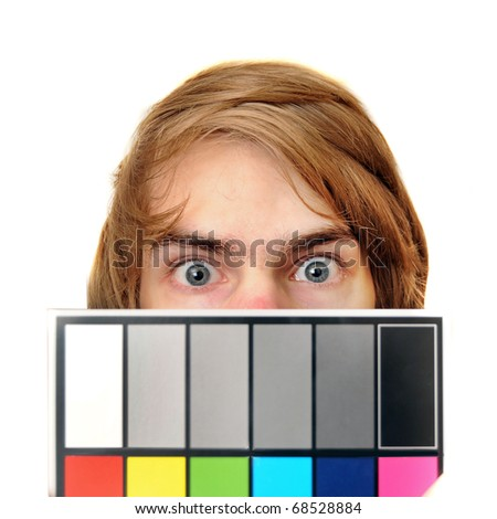 A male production assistant holds up a white balance card with test colors on it to calibrate the colors for photography and videography. - stock photo