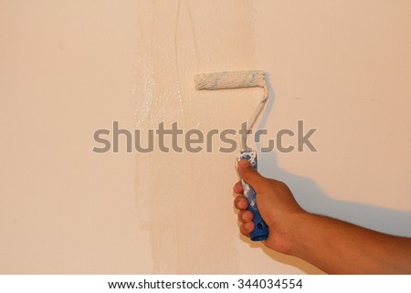 A male right hand is painting the white wall with paint roller and white dye. - stock photo