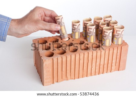 "A male's hand introducing euro notes into the holes of a perforated brick as if it was a piggy bank or a place to ""grow"" notes (metaphor for ""brick investing/real estate investing"" or mortgage). - stock photo"