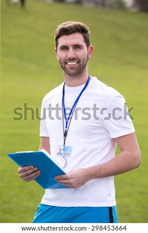 A male sports teacher stands outdoors on a field, he is holding a clipboard. - stock photo