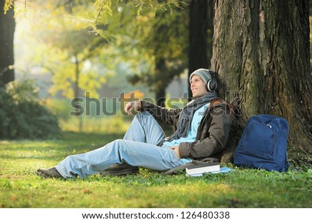 A male student relaxing and listening music seated on a grass in the city park - stock photo
