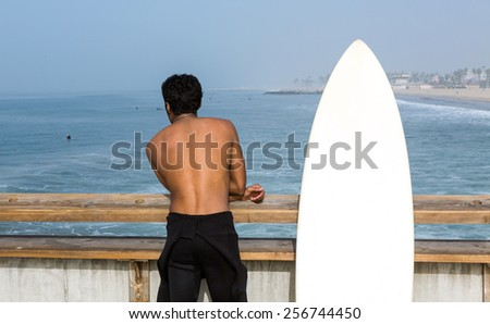 A male surfer with a wetsuit pulled down to his waist and a surfboard next to him, stands on a pier overlooking the ocean below. - stock photo