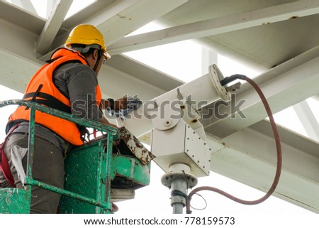 A male technician doing maintenance work by inspecting and cleaning an outdoor security surveillance camera