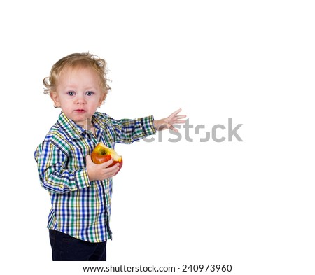 A male toddler holds an apple and points. He has a bite in his mouth.  - stock photo