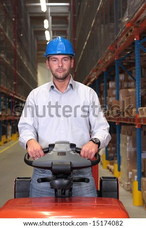 A male warehouse worker, driving a small forklift in the warehouse.