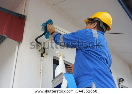 A male worker doing a maintenance work by cleaning and inspecting security camera.