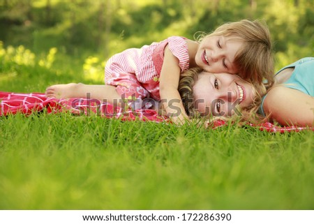 a Mama and her little daughter on the grass - stock photo