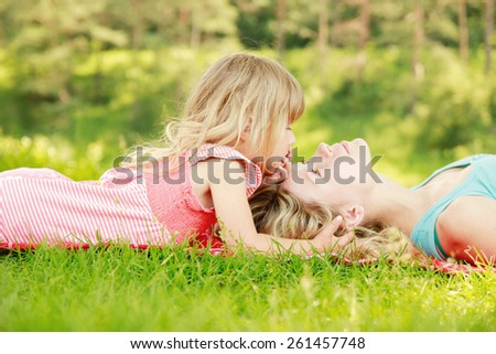 a Mama and her little daughter playing on grass - stock photo