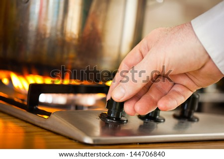 A man adjusting the flame on the top burner of his stove. - stock photo