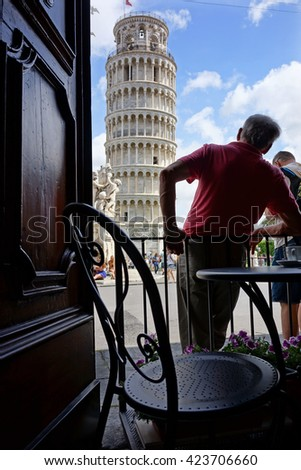 A man admiring the Leaning Tower of Pisa, viewed from a cafe, Tuscany, Italy - stock photo