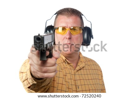A man aims a handgun while wearing proper safety equipment such as safety glasses and hearing protection.