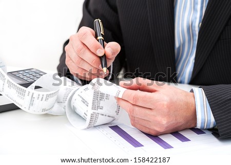 A man analysing a long receipt with his expenses