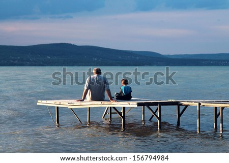 A Man and a boy sitting on the pier