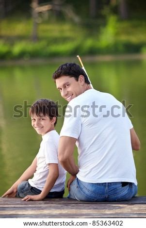 A man and a boy with a fishing rod on the lake - stock photo