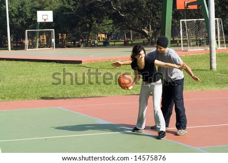 A man and a woman are playing on a park basketball court.  The woman is dribbling the basketball and blocking the man.  They are looking away from the camera.  Horizontally framed shot.