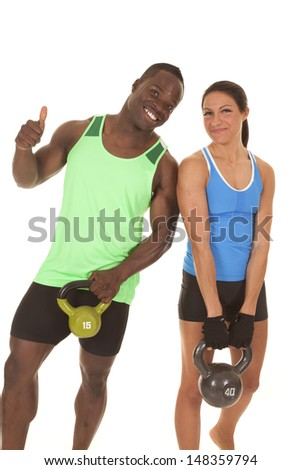 A man and a woman are smiling holding some weights. - stock photo