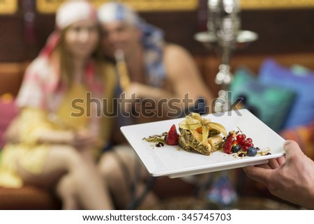 A man and a woman blurred in background waiting for a plate of exotic fruit while smoking water pipe