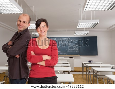 A man and a woman cheerfully smiling on a classroom - stock photo
