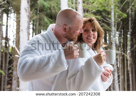 a man and a woman enjoying  a cup of coffee in the morning - stock photo