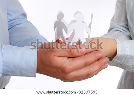 A man and a woman holding paper people, close-up, isolated on white - stock photo