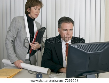 A man and a woman in a workplace setting appearing to be working together. - stock photo