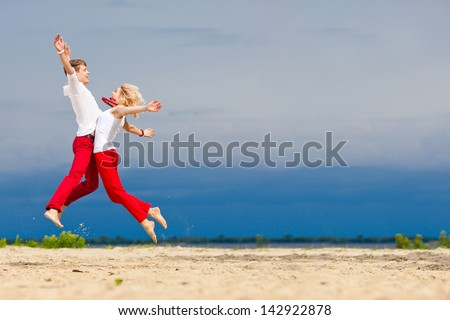 A man and a woman, jump towards each other. Lovers, honeymoon, family look. Beautiful young couple on the beach. Loving couple having fun on nature. Love, romance, fun. Red and white clothes. - stock photo