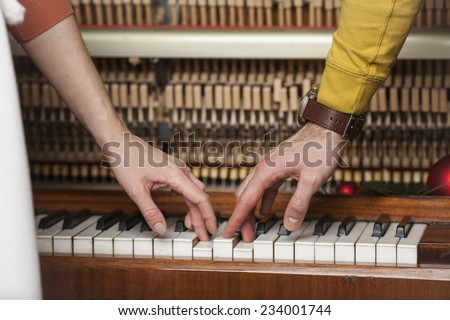 a man and a woman playing the piano together. close-up