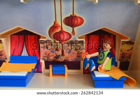 A man and a woman staying at living room watching tv. Alcobendas, Spain. August 3, 2014 man alone goes to bed. Playmobil toy line exist since 1975 and is produced by the german company Brandtaetter. - stock photo