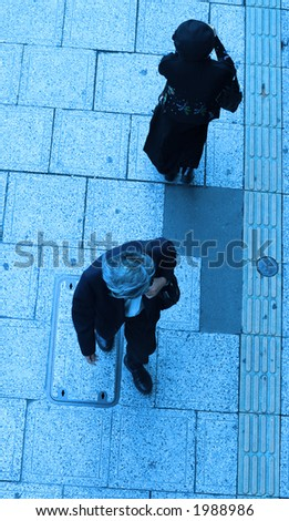 A man and a woman walking in different directions on a city street-upper blue view