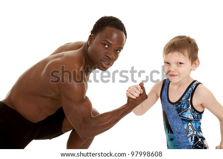 A man and child arm wrestling to see who is stronger.