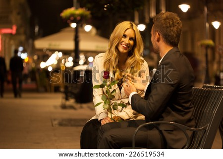 A man and his beutiful date talking on a bench in the evening - stock photo