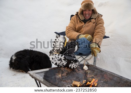 A man and his dog huddles by a fire toasting a marshmallow on a stick while fully surrounded by snow. - stock photo