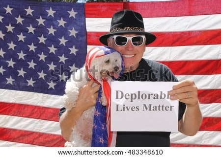 A man and his dog poses in front of am American flag with a Deplorable Lives Matter sign.With his dog.