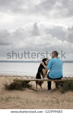 A man and his dog sitting on a bench on a beach