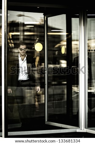 a man and revolving doors in business center - stock photo