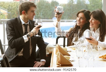 a man and two young woman at table of ristaurant - stock photo