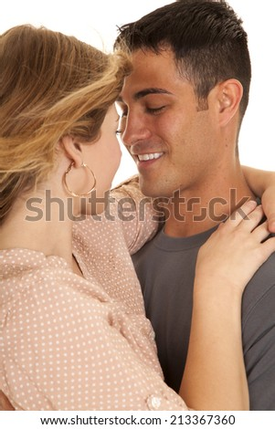 A man and woman cuddling close getting ready to kiss. - stock photo