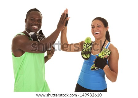 A man and woman giving a high five with running shoes around their necks. - stock photo