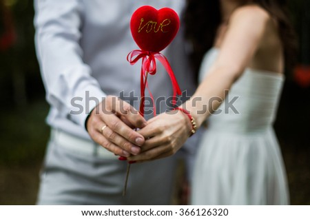a man and woman holding a heart in his hands, the love between a man and a woman, - stock photo
