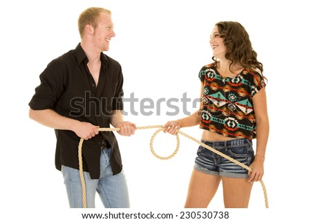 a man and woman playing tug of war with a rope, with smiles on their faces. - stock photo
