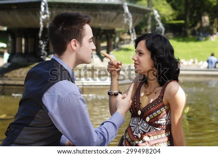 A man and woman pointing at each other arguing. - stock photo