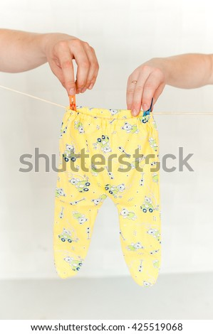 a man and woman's hand pinning a romper suit onto the rope - stock photo