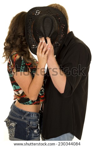 A man and woman sneaking a kiss behind a western hat. - stock photo