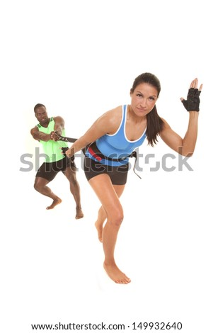 a man and woman training on running using a band. - stock photo
