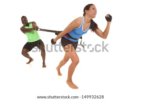 A man and woman training running using a resistance band. - stock photo
