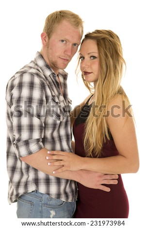 A man and woman with their arms around each other looking. - stock photo