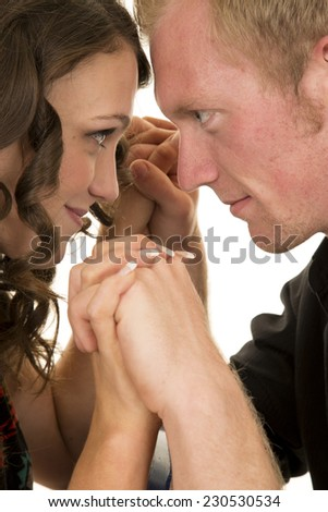 a man and woman with their heads together and hands clasped. - stock photo