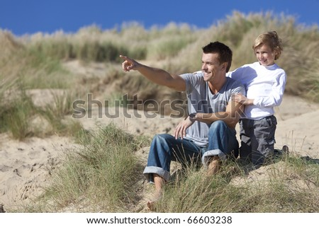 A man and young boy, father and son, sitting down and having fun in the sand dunes of a sunny beach, the father is pointing into the distance.