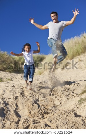 A man and young girl, father and mixed race daughter, playing and having fun jumping in the sand dunes of a sunny beach